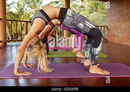 Side view of young women sportswear working out in gym, doing backbend bridge Pose. Fitness females doing chakrasana - Stock Photo