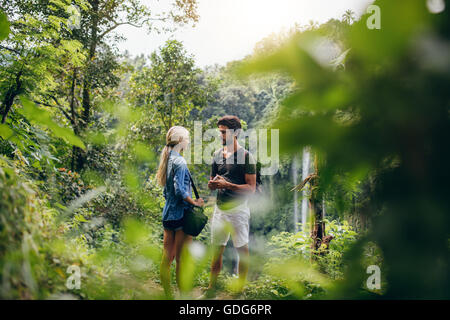 Outdoor shot of young man and woman standing together on a cliff and talking. Couple of hikers together in a forest - Stock Photo