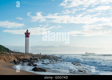 DURBAN, SOUTH AFRICA - MARCH 12, 2016: Umhlanga Rocks Lighthouse with fishermen and people walking on the promenade. - Stock Photo