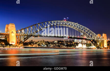 Side view of Sydney Harbour bridge architectural landmark at sunset. Illuminated arch of the bridge reflecting in - Stock Photo
