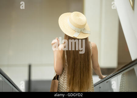 Young beautiful long-haired customer woman wearing a hat and cute polka dot summer dress carrying shopping paper - Stock Photo