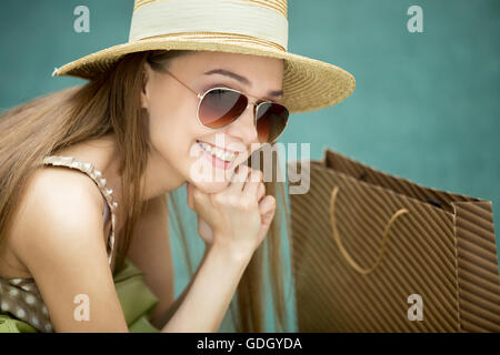Headshot of young pretty shopper long-haired woman wearing summer hat and trendy sunglasses sitting on green background - Stock Photo
