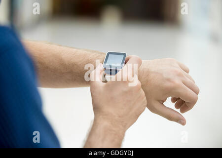 Close-up of hand of young man touching display on his smart watch with blank black screen, using internet, messaging, - Stock Photo