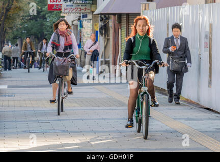 Cycling in the city of Osaka Japan along one of the many cycle paths which are generally kept separate from road - Stock Photo