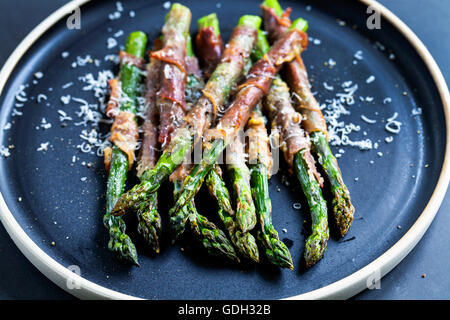 Grilled asparagus wrapped in Parma ham with parmesan, sage and thyme - Stock Photo