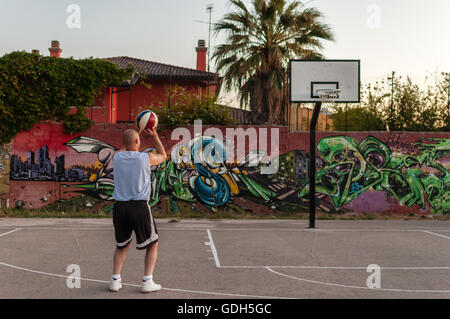 Basketball player in city playground at sunset - Stock Photo