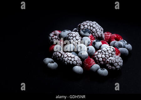 forest fruits frozen, raspberries, blueberries and blackberries on a black stone table - Stock Photo