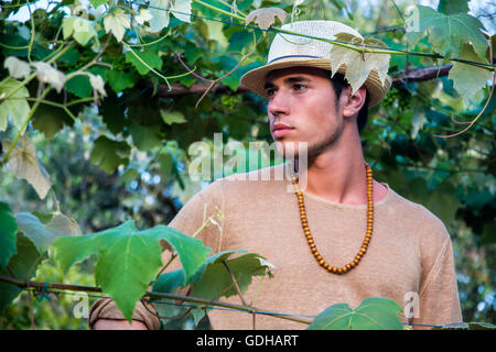 Side view of handsome young man in hat toching vine leaves in garden in sunlight - Stock Photo