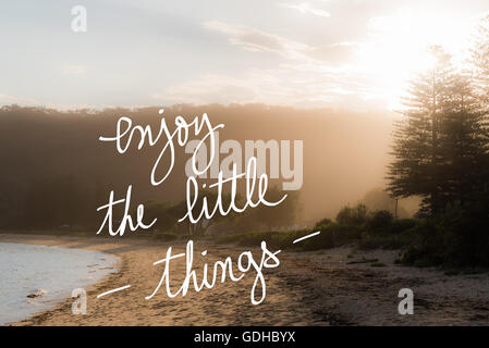 Enjoy The Little Things message. Handwritten motivational text over sunset calm sunny beach background with vintage - Stock Photo
