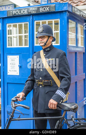 Woodhall Spa 1940s Festival - Policeman dressed in 1940s uniform stood by a traditional police telephone box - Stock Photo