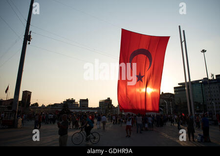Istanbul, Turkey. 17th July, 2017. The sun goes down behind a giant Turkish flag at Taksim Square in Istanbul, Turkey, - Stock Photo
