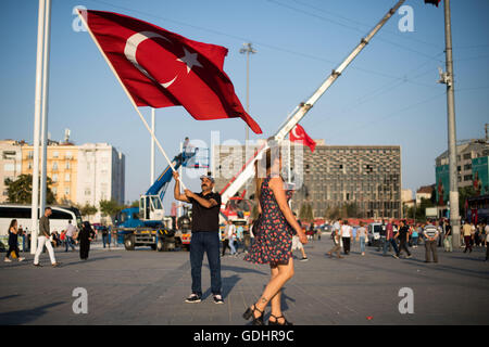 Istanbul, Turkey. 17th July, 2017. A man holds a Turkish flag at Taksim Square in Istanbul, Turkey, 17 July 2017. - Stock Photo