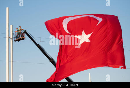 Istanbul, Turkey. 17th July, 2016. Workers fly a giant Turkish flag at Taksim Square in Istanbul, Turkey, 17 July - Stock Photo