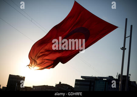 Istanbul, Turkey. 17th July, 2016. The sun goes down behind a giant Turkish flag at Taksim Square in Istanbul, Turkey, - Stock Photo