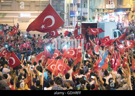 Istanbul, Turkey. 17th July, 2016. People shout slogans and hold flags during a demonstration at Taksim Square in - Stock Photo