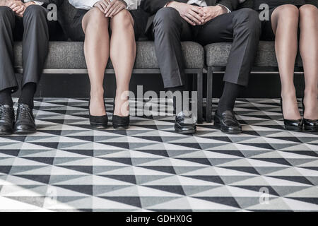 Business people waiting for job interview sitting in a row - Stock Photo