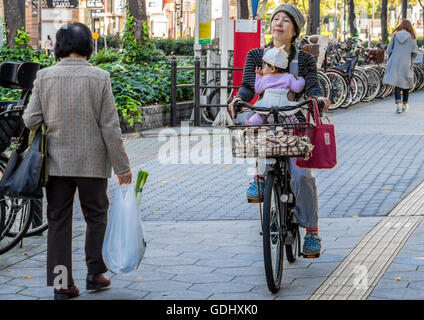 Mother with child cycling in the city of Osaka Japan along cycle paths which are generally kept separate from road - Stock Photo
