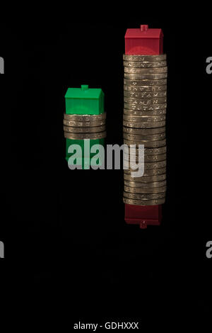House / housing / property price inflation concept. Colorful toy houses placed on stacks of pound coins on black - Stock Photo