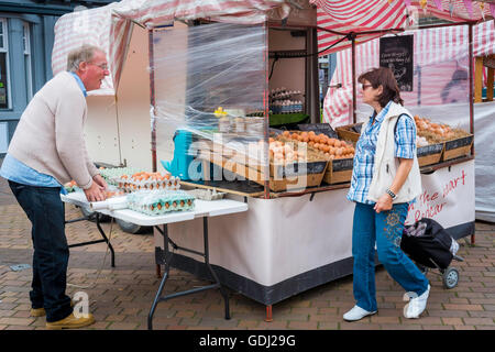 Woman customer buying eggs on a specialist farmer's market stall in North Yorkshire - Stock Photo