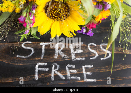 Words Stress Free with Summer Flowers on a Rustic Wooden Background. - Stock Photo