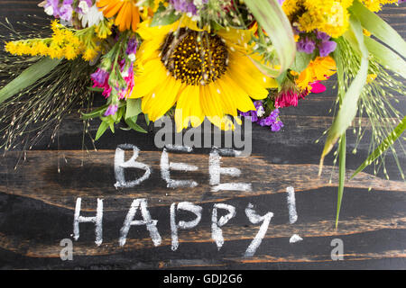 Words Bee Happy with Summer Flowers on a Rustic Wooden Background. - Stock Photo