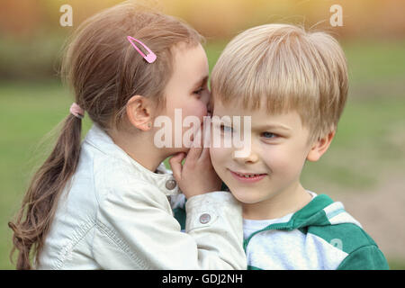 boy and girl playing outside - Stock Photo