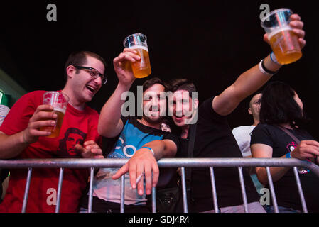 Guys with beer in audience posing for camera during music concert at Festival Lent, Maribor, Slovenia, 2015 - Stock Photo