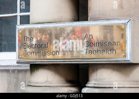 Brass sign on the offices of the Electoral Commission in Edinburgh, with reflection of people. - Stock Photo