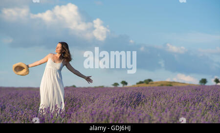 Beautiful young woman wearing a white dress celebrating the beauty of life standing in the middle of a lavender - Stock Photo