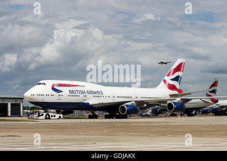 Row of British Airways airplanes with another aircraft approaching in the background at London Heathrow Airport - Stock Photo