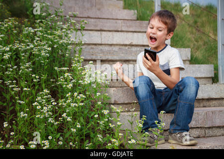 Winning a mobile game. Happy boy looking shocked with opened mouth and eyes on a cell phone. Outdoor. Mobile gaming - Stock Photo