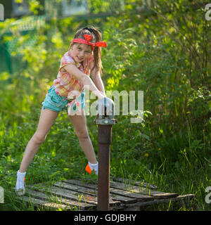 Little naughty girl near the water pump in the village. - Stock Photo