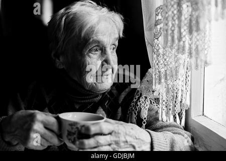Elderly woman drinking tea looking out the window. Black-and-white photo of high contrast. - Stock Photo