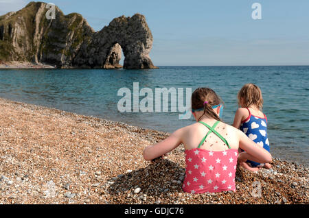 Children playing on the beach next to Durdle Door, Lulworth, Dorset - Stock Photo