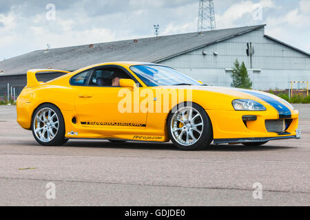 Kotka, Finland - July 16, 2016: Yellow sporty Toyota Supra A80 goes down the street in town - Stock Photo