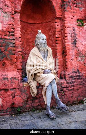 KATHMANDU, NEPAL - OCTOBER 21, 2015 : Wandering  Shaiva sadhu (holy man) with white face painting in ancient Pashupatinath - Stock Photo