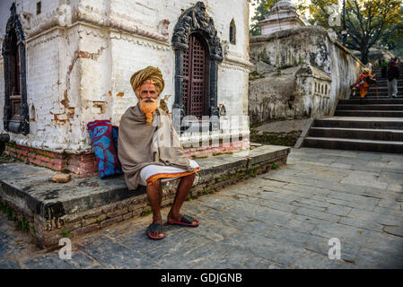 Wandering  sadhu baba (holy man) with traditional long hair in ancient Pashupatinath Temple - Stock Photo
