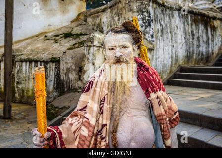 Portrait of wandering  Shaiva sadhu (holy man) with white face painting in ancient Pashupatinath Temple, Kathmandu, - Stock Photo