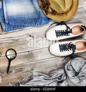 Set of travel items including shoes, scarf, jeans, magnifying glass and straw hat. Overhead view. Flat lay.