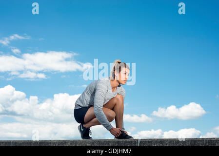 fit woman tying up her shoelaces on her trainers - Stock Photo