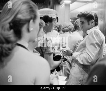 Elvis Presley signing autographs at the Fox Theater, Detroit, Michigan, May 25, 1956. - Stock Photo