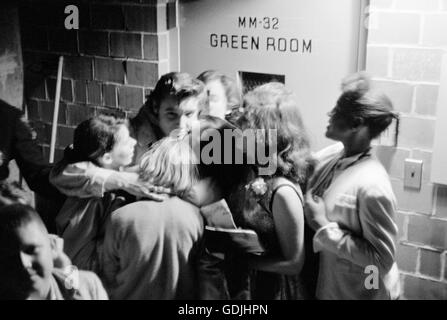 Elvis Presley hugging a group of fans backstage after a performance at the University of Dayton Fieldhouse, May - Stock Photo