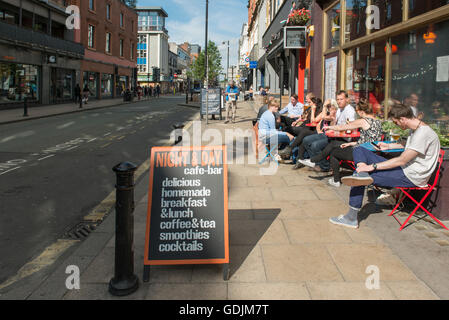 People enjoying a drink outside Night and Day cafe on Oldham Street in the Northern Quarter area of Manchester. - Stock Photo