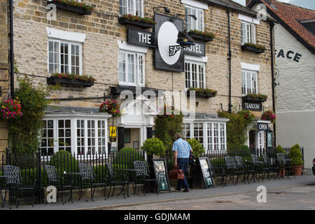 Exterior of Black Swan Hotel, Helmsley, North Yorkshire - one man entering this popular boutique hotel in historic, - Stock Photo
