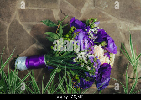 wedding bouquet. golden rings and two glasses of shampagne on the background of green grass and stone. - Stock Photo