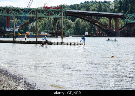 Stand up paddle boarders on Willamette River in front of the Sellwood Bridge, Portland Oregon - Stock Photo
