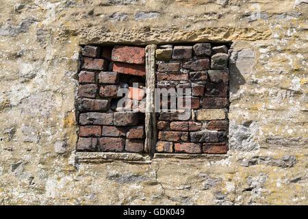 Bricked up window of stone barn, - Stock Photo