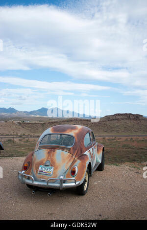 Rusty Volkswagen Beetle overlooks mountains in Kingsman, Arizona on route 66 - Stock Photo