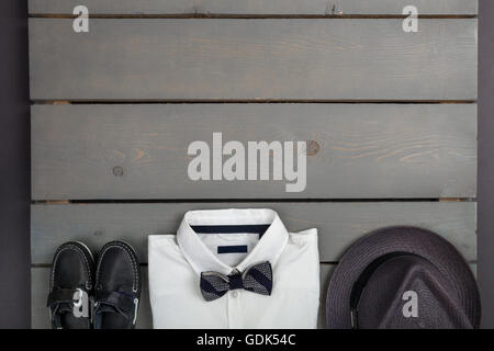 Kids fashion clothes. Grey fedora, white shirt, black bow tie and boat shoes for boy. Top view. Copy space. Frame - Stock Photo