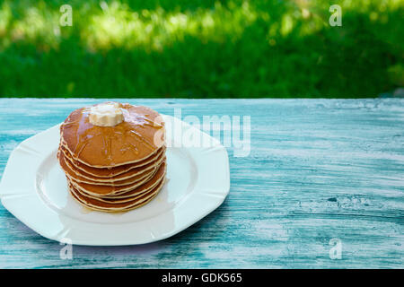 Pancakes with butter and honey on white plate on blue wooden background in garden or on nature background. Stack - Stock Photo